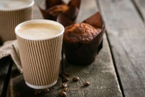 A hot latte and a muffin on a table